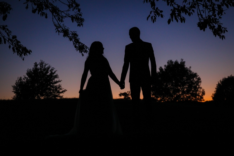 Couple holding hands in front of the sunset at Beaumanor Hall Loughborough