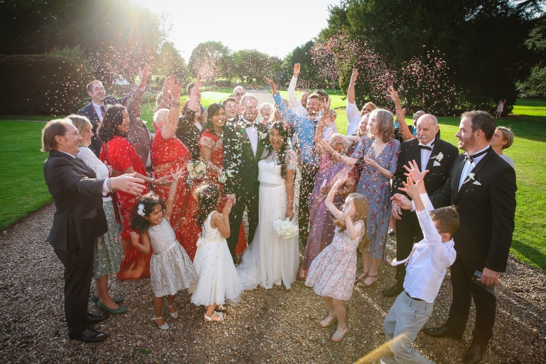 Wedding guests throwing confetti over bride and groom at Beaumanor Hall Loughborough